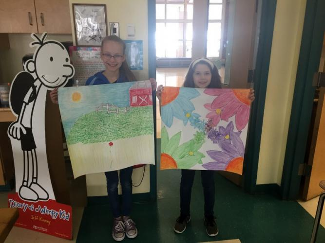 Reed Intermediate School students Bree Hintze, left, and Lola Kessler hold their artwork selected for the Impressions of Nature art exhibit.