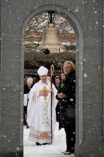 As a moderate snow continued to fall, Bishop Frank J. Caggiano looks on as First Selectman Pat Llodra rings one of several bells temporarily installed for a postmemorial ceremony at St Rose of Lima Parish on the one-year anniversary of 12/14.  …