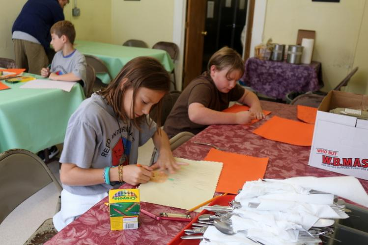 Reed Intermediate School students Rachael Albrecht, front left, and John Jensen, front right help decorate placemats at the Dorothy Day Hospitality House.