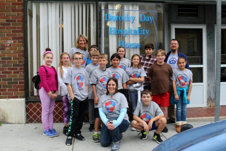 Reed Intermediate School teachers Karen King, standing back left, Jessica O'Connell, kneeling in the front, and Sean O'Connell, standing back right, pose for a picture in front of the Dorothy Day Hospitality House on September 30 with student volunteers.