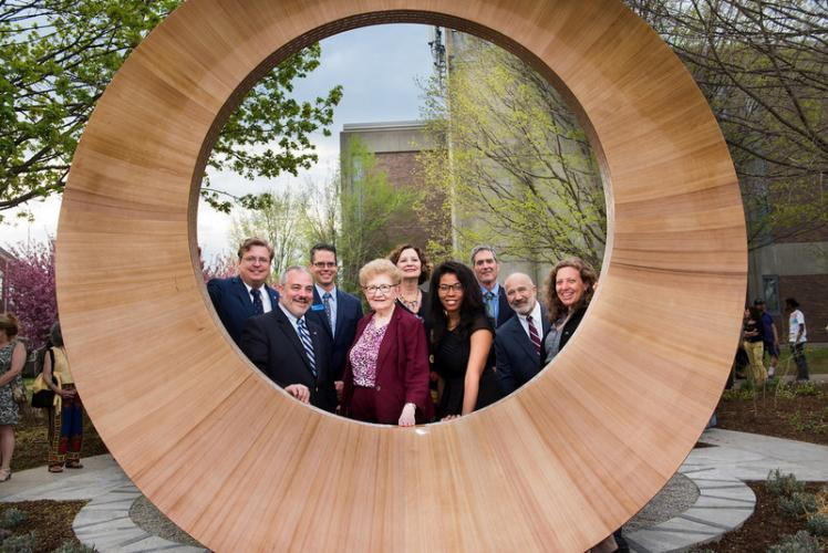 Southern Connecticut State University (SCSU) officials, as well as individuals involved with the establishment of a memorial to honor victims of the 2012 Sandy Hook Elementary School shooting, look through the memorial during a May 4 ceremony…