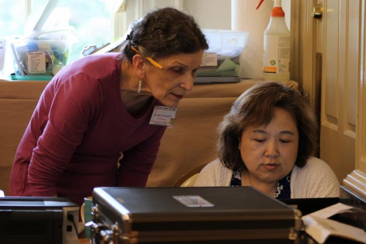Newtown Bridge Club Manager Susan Fronapfel, left, speaks with Weiling Zhao during The Longest Day. Ms Zhao was game director for the event's morning session.  (Bee Photo, Hicks)