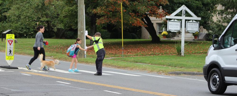 A Hawley School student gives Traffic Agent Kat Holick a high five as her mother escorts the young girl to school one recent morning.  (Bee Photo, Hicks)
