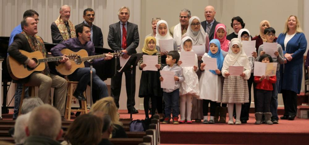 """NCC Senior Pastor Matt Crebbin, NCC member Tim Stan (partially hidden) and Jim Allyn led the children's group in singing """"This Land Is Your Land."""" The group was joined by some of the adult clergy leaders also participating in the interfaith…"""