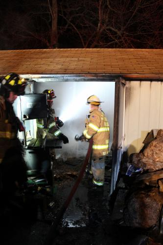 Sandy Hook Volunteer Fire & Rescue Company First Assistant Chief Mike Burton applies foam to the interior of the shed at 24 Poplar Drive. Firefighters used 3,300 gallons of water and three gallons of foam to extinguish the blaze.  (Bee Photo, Hicks)