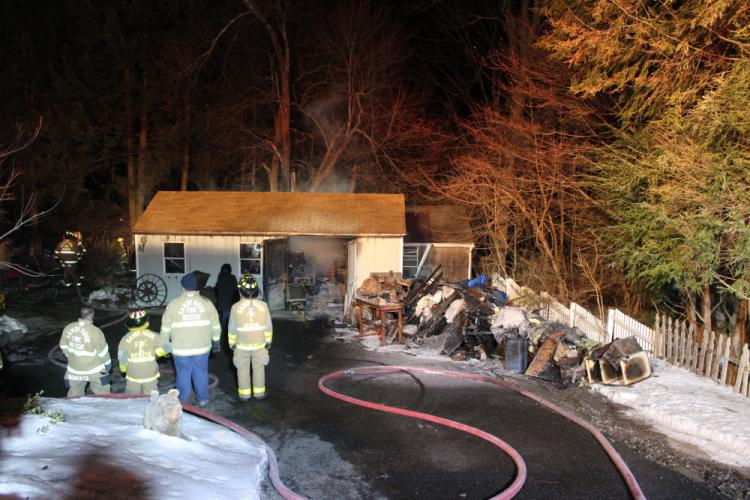 Firefighters stand near the workshop that burned Thursday night on Poplar Drive in Sandy Hook, while its contents are spread out along the driveway.  (Bee Photo, Hicks)