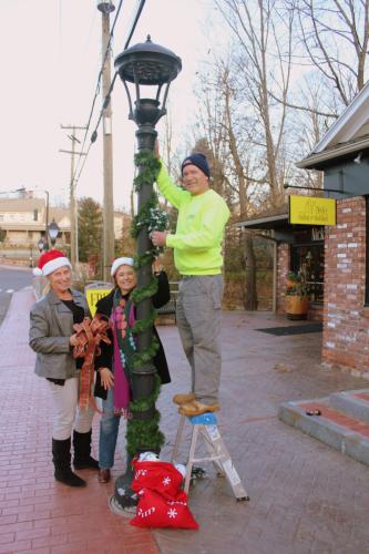 SHOP members, from left, Maribeth Hemingway, Julie Friend, and Mike Burton previewed some of the decorations that will be hung from the lamp poles in Sandy Hook Center on November 24. Residents are being invited to adopt a lamppost, and participate…