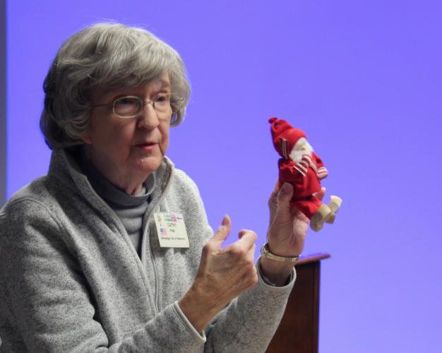"""Cathy Hugo holds up a """"more modern tomte,"""" she said. Contemporary tomtes look more like Santa Claus, she explained. Earlier versions of the mischievous spirits featured long white beards and a tall knit cap in red or another bright color, similar to…"""