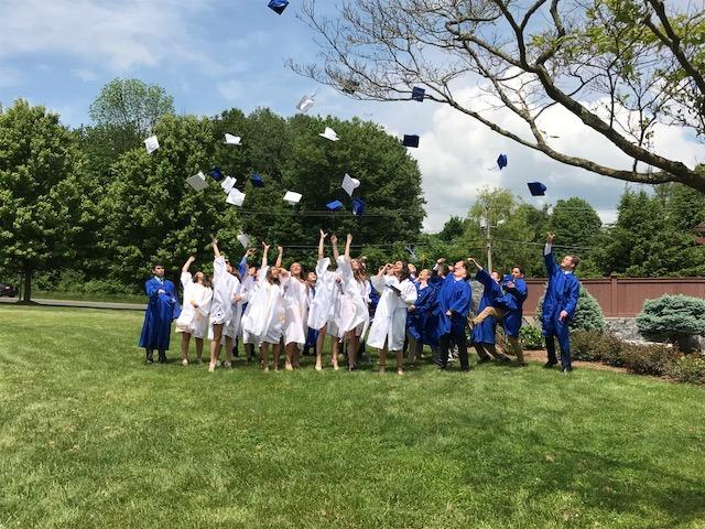St Rose of Lima School Class of 2018 graduates toss their caps in the air on the front lawn of the church following the graduation mass and ceremony on June 2. (Laura Moulder photo)