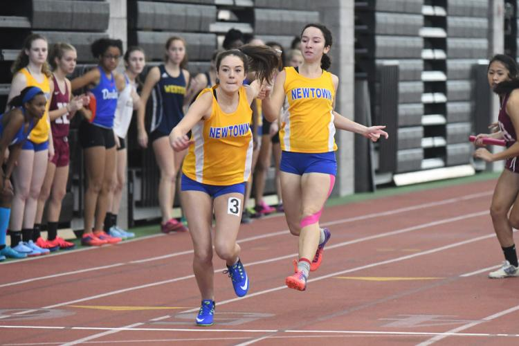 Jackie O'Leary, right, passes the baton to Grace Pettinelli during the 4x200 relay race at the SCC meet on January 13. (Krista Benson photo)