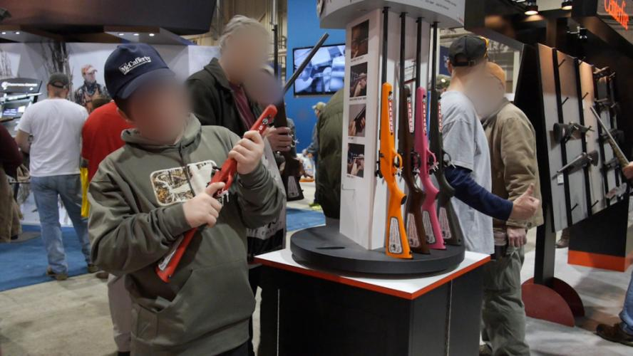 "A youth at the 2014 Great American Outdoors Show in Harrisburg, Penn., checks out a child-sized rifle. Parents should be concerned, says Josh Sugarman, author of the VPC report ""Start Them Young,"" of the gun industry's push to market firearms to…"