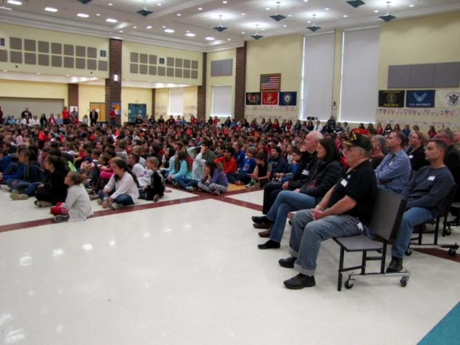 Invited guests and veterans sit, right, at an assembly at Reed Intermediate School held to honor them and Veterans Day.