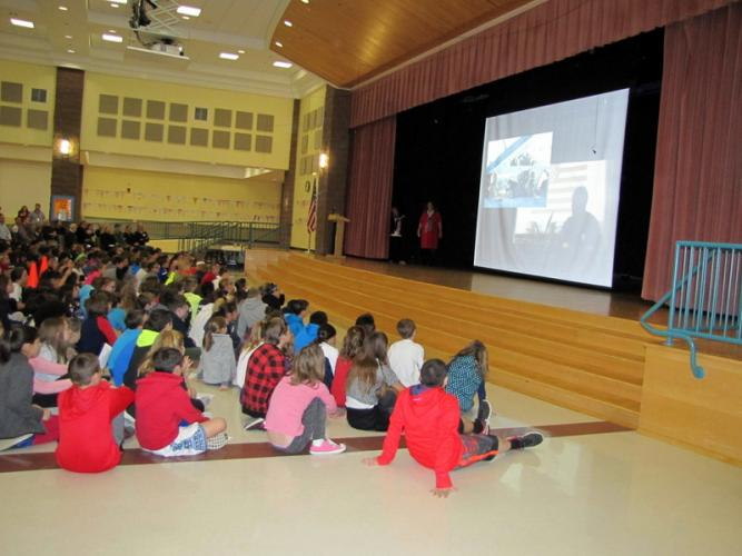 Reed Intermediate School students watched a video at the Veterans Day assembly, with Assistant Principal Jill Beaudry, standing on stage, looking on. (Sabrina Watson photo)