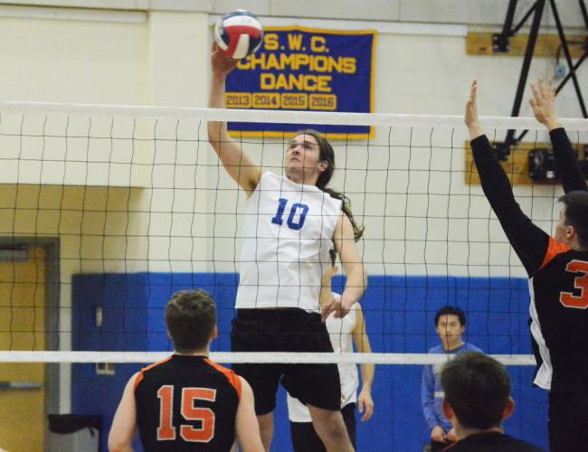 Silas Decker goes up to spike the ball over the net during Newtown's win over Shelton. (Bee Photo, Hutchison)