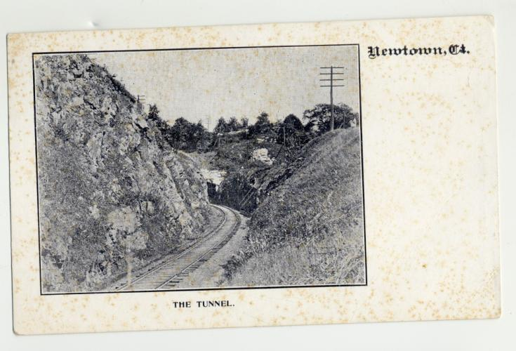 """An old postcard titled """"The Tunnel"""" shows a railroad track in Newtown slipping into a carved out area at the bottom of a hillside."""