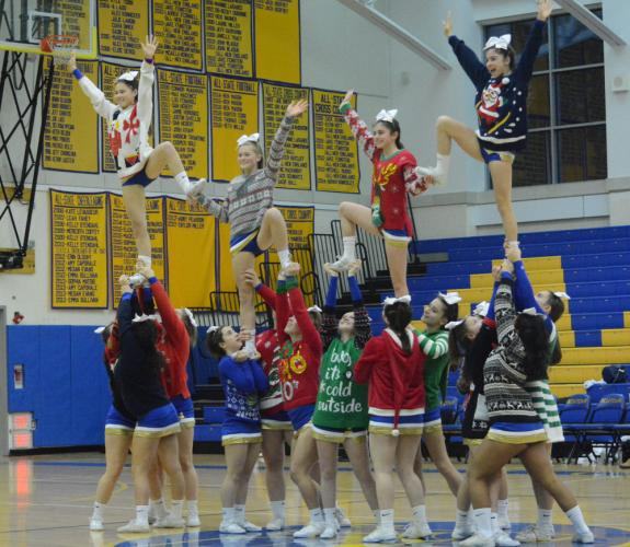 NHS cheerleaders, decked out in holiday sweaters, entertain the fans during a basketball game this winter. Cheer Coach Susan Bridges received Coach of the Year accolades. (Bee Photo, Hutchison)