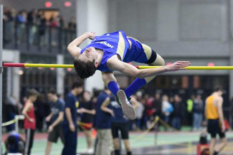 Zach Crebbin high jumps during postseason action this winter. Crebbin broke the NHS record, clearing the bar at 6-foot-3 during the New England championships. (Krista Benson photo)