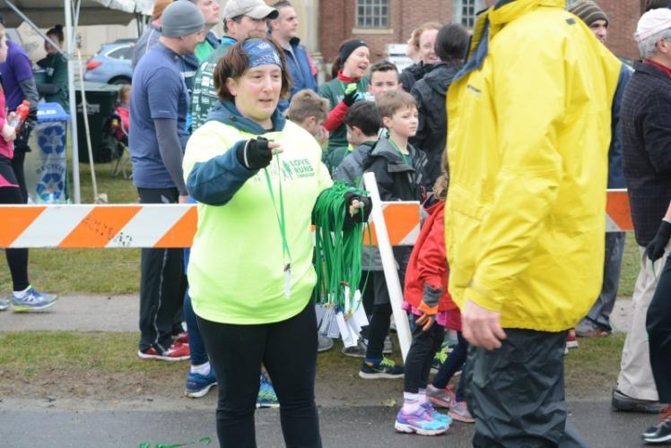 Volunteers, including Laurie Borelli, hand finishers Bens' Bells Kindness Coins at the Sandy Hook 5K. -Bee Photo, Hutchison