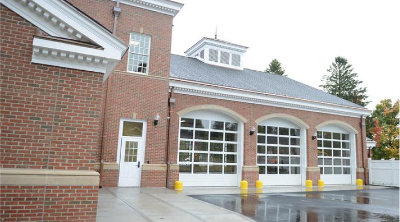A six-bay garage for the new Newtown Volunteer Ambulance Corps headquarters is set up as a pass-through, with three bay doors in front and three in back. This back view connects to common parking areas on the Fairfield Hills campus. A series of…