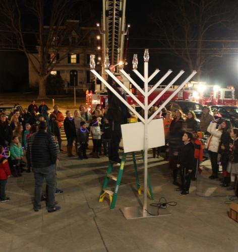 Rabbi Sholom Deitsch lights a candle on a giant menorah in front of Edmond Town Hall last year during a community menorah lighting event. Congregation Adath Israel and Hadassah of Greater Newtown/Danbury will co-sponsor a similar event this evening,…