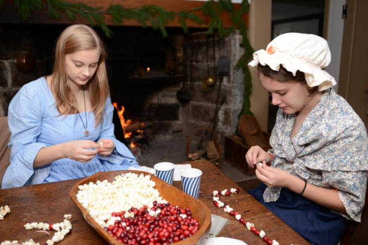 With pins gripped in nimble fingers, Amelia Schill and Caitlin Farrell carefully strung cranberries and popped corn into a decorative garland during last year's Newtown Historical Society Holiday Open House.  (Bee file photo)