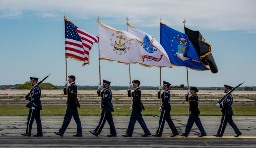 The Rhode Island Air National Guard Honor Guard marched onto the airport tarmac and stood at attention during the National Anthem.