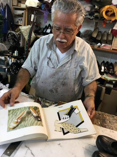 Anthony Paravalos flips through illustrations of shoes that he has designed. -Bee Photo, Bobowick