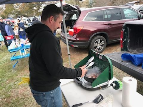 Eric Phaneuf cooks during a tailgate event at the Yale-Harvard game. Mr Phaneuf attended with friends, including Steve George, a Newtown High football coach. (Steve George photo)