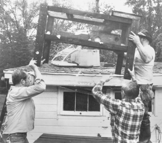 """The only hints in this old Bee photo come from writing on the back that says: """"5-3-84 flood."""" The men appear to be lifting a pet hutch onto a roof.  (Bee file photo)"""
