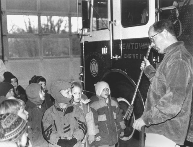"It looks like some well bundled up youngsters are getting a lesson on tools used by firefighters. The only hints about this picture, though, are words written on the back: ""Touring Hook and Ladder."" Does anyone recognize the firefighter or any of…"