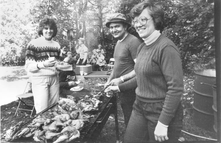According to what is written on the back of this image, these people, and a band in the background, were attending the 1984 Sandy Hook Organization for Prosperity picnic. SHOP's chicken barbecue is being tended by Bill and Charlotte (last name…