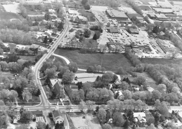 An aerial image of Newtown dated May 25, 1985, captures Main Street, with the flagpole in the lower left corner, along with Trinity Church and its lower driveway, Newtown Congregational Church (as it still was at that time), and Queen Street…