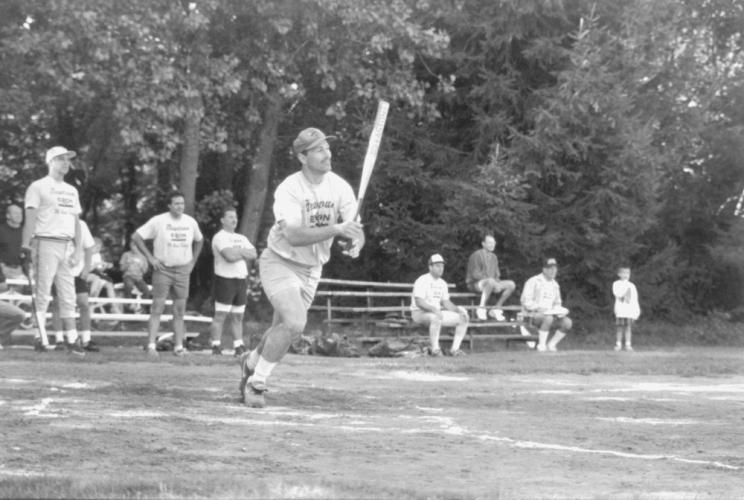 Little information is written on the back of this old Bee photo found in an envelope. Handwriting indicates Men's Slow Pitch, followed by what may say Sunday League, but is not legible. The uniforms say Newtown Exxon. The man at bat appears to have…