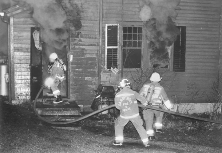 An undated photo in an old Bee envelope shows Sandy Hook Fire & Rescue members actively battling a fire blowing thick smoke through the door and windows.