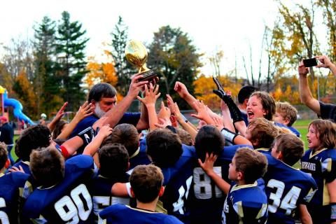 Members of the fourth grade football team celebrate their Colonial League Orange Bowl championship.