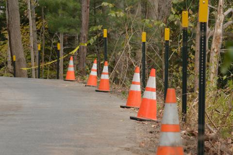 Traffic cones, reflectors, and caution tape along the side of the road on Dayton Street.