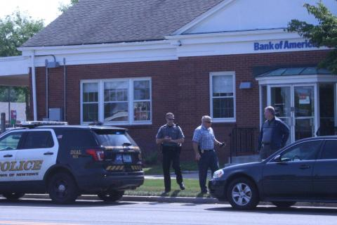 Two town police detectives and a patrolman are seen in front of the Bank of America on Queen Street following a bank robbery there in August. Police captured the alleged robber as he fled on foot from the bank.  (Bee file photo)