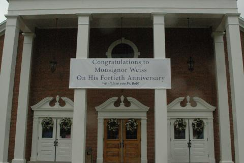 A handsome banner was suspended from the columns on the façade of St Rose Church, congratulating Monsignor Robert Weiss on the 40th anniversary of his ordination.