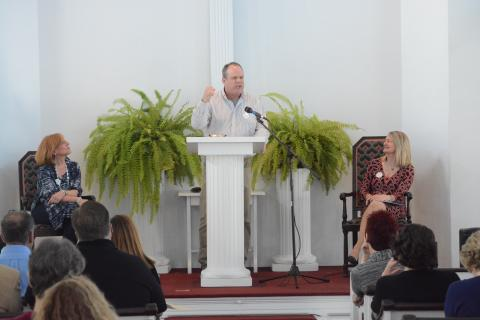 """The Reverend Matt Crebbin recites Garrison Keillor's """"Casey at the Bat (Road Game)"""" during the Newtown Cultural Arts Commission-sponsored Risk A Verse event at Newtown Meeting House on April 23. Rev Crebbin is flanked by event organizers Lisa…"""