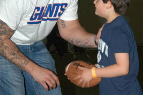 Now that's a big Diehl! New York Giants player David Diehl gives some advice to an up and coming football player at Newtown Youth Academy on April 18.