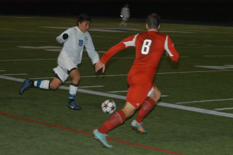 Blake Jarvis runs with the ball during Newtown's SWC tourney opener against Masuk on October 26. Newtown prevailed for a 1-0 win following a pair of ten-minute overtimes and a round a penalty kicks.