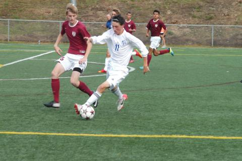 Newtown's Clay Gattey (No. 11) dribbles the ball as a Bethel player defends during a 1-1 tie on September 21. Gattey scored Newtown's lone goal.