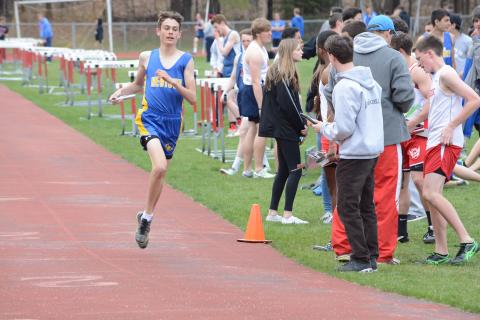 Brenden Reeds competes in a relay race during Newtown's visit to Masuk of Monroe on April 27.