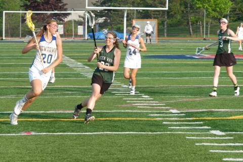 Julia Trudell moves with the ball during Newtown's 15-10 win over New Milford in the SWC tourney semifinals on May 21. Trudell netted five goals in the triumph.