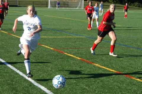 Sarah Lynch races down the sideline with the ball during Newtown's 4-1 win over Masuk on September 19. Lynch scored once and helped set up two other goals in the triumph.