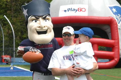 Steve George, coach of the Newtown High football team, with his son Peyton, visit with the Patriots mascot during the NFL team's visit to Newtown on May 18.