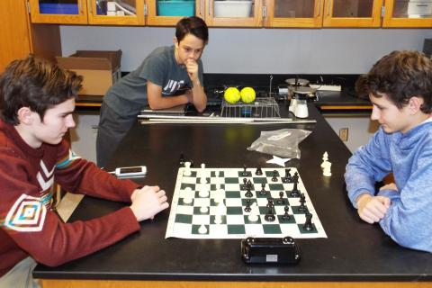 Newtown High School Chess Club members Thomas Hartley and Miles Martiska play a game of chess, while Bryce Bisset watches in suspense. (Bee Photo, Silber)
