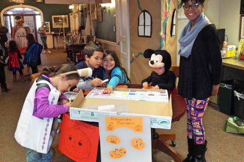 Pictured from left are neighbors Mikaela Martins, Andy Class, Gabbie Class, and Christian Martins designing paper jack-o'-lanterns with Young Adult Council member Chloe Rackley. (Bee Photo, Silber)