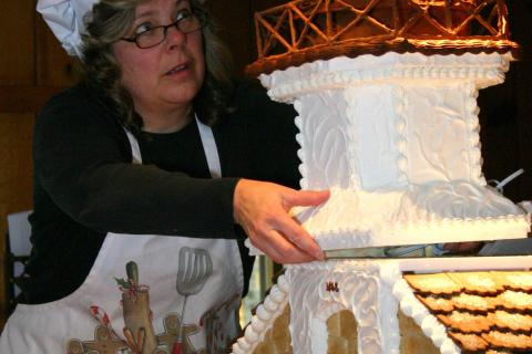 "For this year's contest, Ms Ball — seen here placing the topper on 2011's ""Sugar Cookie Sheffield Island"" — looked back at the strengths of her first lighthouse. Children responded to candy, cookies, icing, &ldquo…"