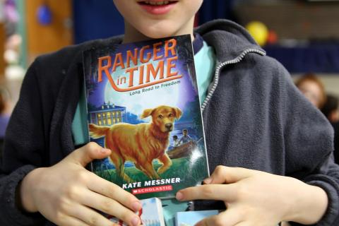 Hawley Elementary School fourth grader Kyle Boughan brought three of his copies of author Kate Messner's books with him to the April 7 Skype session. (Bee Photo, Hallabeck)